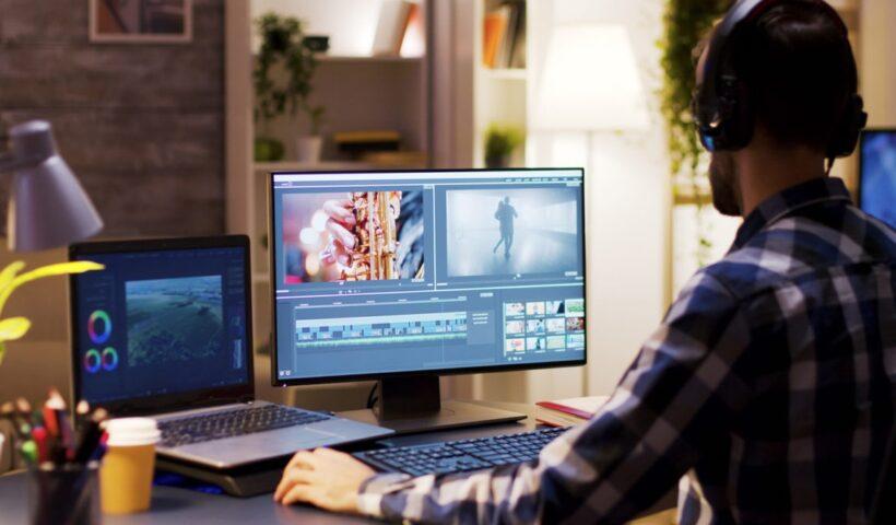 Jeun homme travaillant sur un montage vidéo avec son ordinateur